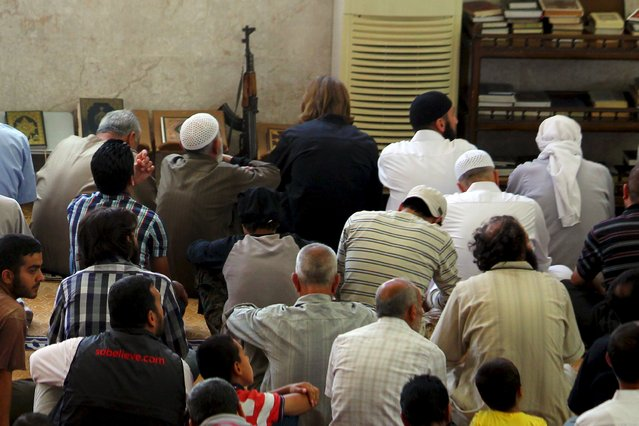 Civilians and rebel fighters pray inside a mosque during the last Friday prayer of the holy month of Ramadan in Idlib city, Syria July 10, 2015. (Photo by Ammar Abdullah/Reuters)