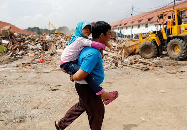 A man carries his daughter as he walks near machinery demolishing illegal houses at Luar Batang fisheries village in Jakarta, Indonesia, April 11, 2016. (Photo by Reuters/Beawiharta)