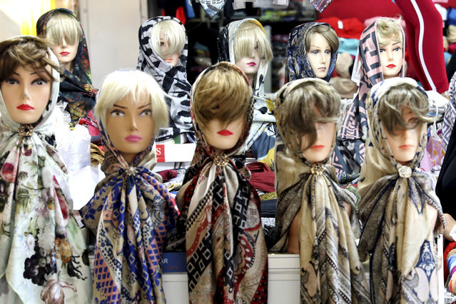 In this Wednesday, July 3, 2019 photo, mannequins with headscarves are placed at a market in downtown Tehran, Iran. (Photo by Ebrahim Noroozi/AP Photo)