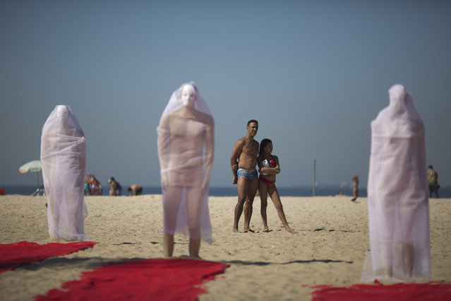 Beachgoers look at a trio of veiled wrapped mannequins that are part of a a protest staged by Rio de Paz activists on Copacabana beach to press for clarifications on missing persons including a bricklayer who recently disappeared, in Rio de Janeiro, Brazil, Wednesday, July 31, 2013. (Photo by Felipe Dana/AP Photo)