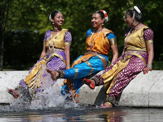 (L to R) Tanis Babu Robert, Dhuwaraha Rajathelakan and Latha Ramajeyam, dancers from the Abhinaya dance group enjoy themselves at Kelvingrove Park as Commonwealth Games recruits are to be given a test run at Glasgow's Mela festival six weeks before the Games. (Photo by Andrew Milligan/PA Wire)