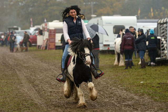 A woman rides a horse through the biannual Stow Horse Fair in the town of Stow-on-the-Wold, southern England on October 24, 2019. (Photo by Oli Scarff/AFP Photo)