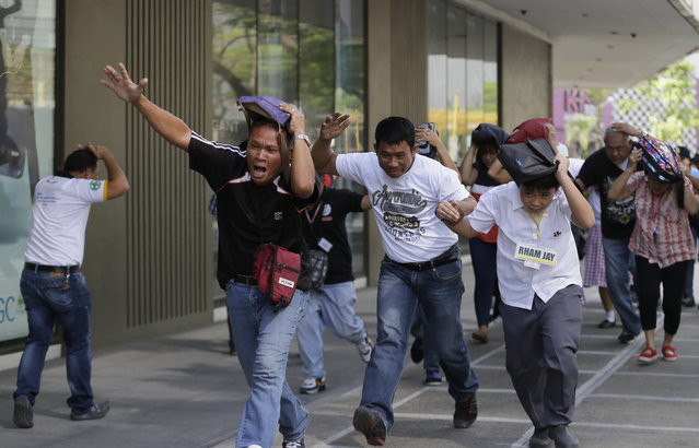 People rush to safety as they simulate a powerful earthquake during a nationwide drill at a commercial center in suburban Taguig city east of Manila, Philippines, Thursday, July 23, 2015. Various earthquake drills took place nationwide as officials and first responders assessed their emergency preparedness. (Photo by Bullit Marquez/AP Photo)