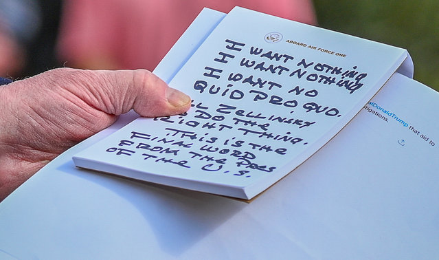 U.S. President Donald Trump holds what appears to be a prepared statement and handwritten notes after watching testimony by U.S. Ambassador to the European Union Gordon Sondland as he speaks to reporters prior to departing for travel to Austin, Texas from the South Lawn of the White House in Washington, U.S., November 20, 2019. (Photo by Erin Scott/Reuters)