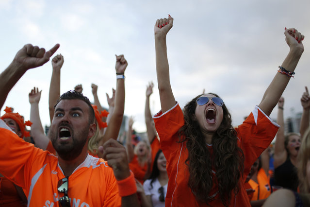 Dutch soccer fans celebrate a goal as they watch the 2014 World Cup soccer match between the Netherlands and Spain which was broadcasted on a large screen at Copacabana beach in Rio de Janeiro, June 13, 2014. (Photo by Pilar Olivares/Reuters)