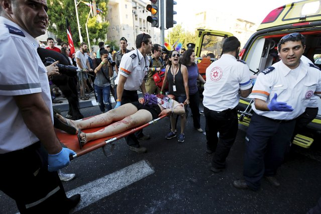 A participant of an annual gay pride parade is treated after an Orthodox Jewish assailant stabbed and  injuring six participants of an annual Gay Pride march in Jerusalem on Thursday, police and witnesses said July 30, 2015. (Photo by Amir Cohen/Reuters)