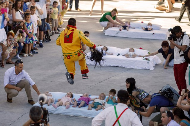 "A man dressed up as the devil jumps over babies lying on a mattress in the street during ""El Colacho"", the ""baby jumping festival"" in the village of Castrillo de Murcia, near Burgos on June 18, 2017. Baby jumping (El Colacho) is a traditional Spanish practice dating back to 1620 that takes place annually to celebrate the Catholic feast of Corpus Christi. During the act – known as El Salto del Colacho (the devil's jump) or simply El Colacho – men dressed as the Devil jump over babies born in the last twelve months of the year who lie on mattresses in the street. (Photo by Cesar Manso/AFP Photo)"