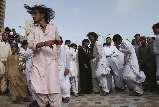 Pakistani Pashtun people perform their traditional dance at Clinfton beach to celebrate Eid al-Fitr holidays in Karachi, Pakistan, Sunday, July 19, 2015. The three-day holidays of Eid al-Fitr marks the end of the holy fasting month of Ramadan. (Photo by Farid Khan/AP Photo)