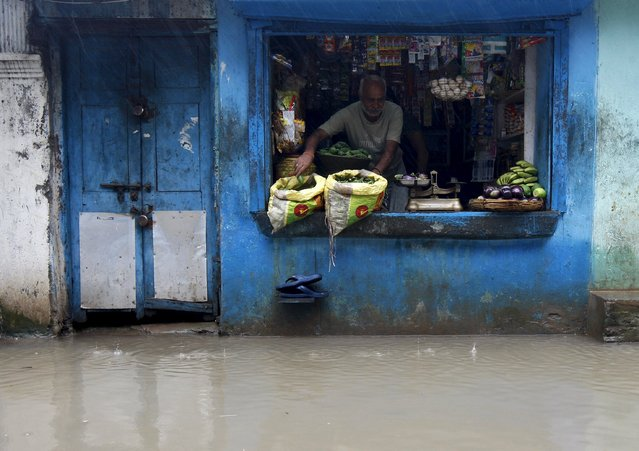 A shopkeeper weighs vegetables inside his flooded shop as it rains in Kolkata, India, August 1, 2015. (Photo by Rupak De Chowdhuri/Reuters)