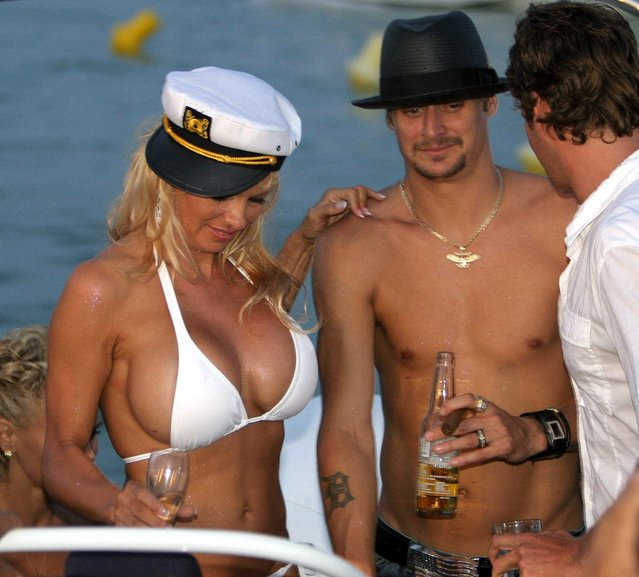 Photo dated 29 July 2006 shows Canadian actress Pamela Anderson (L) sharing a drink with her husband US musician Kid Rock (C) on the day of their wedding on Pampelone's beach in Saint-Tropez, southern France. Anderson said 27 November 2006 that she is divorcing Rock, just four months after tying the knot to the US musician. The 39-year-old blonde s*x symbol confirmed in a five-word statement on her official website that she was splitting with Rock, whom she married in a glitzy St Tropez ceremony in July. (Photo by Eric Estrade/AFP Photo)