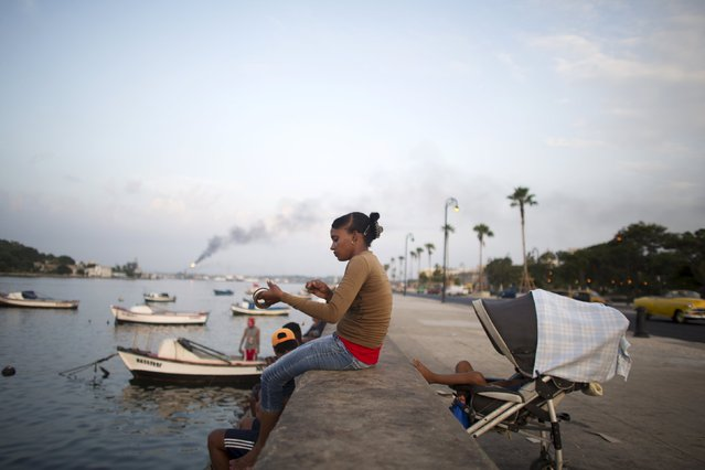 Yanesi Ailan, 23, fishes at the Havana bay's canal as her three-year-old son sleeps in a stroller behind her in Havana, July 31, 2015. (Photo by Alexandre Meneghini/Reuters)