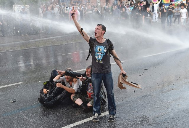 "A protester shouts as riot police use water cannons trucks during the ""Welcome to Hell"" rally against the G20 summit in Hamburg, northern Germany on July 6, 2017. Leaders of the world's top economies will gather from July 7 to 8, 2017 in Germany for likely the stormiest G20 summit in years, with disagreements ranging from wars to climate change and global trade. (Photo by Christof Stache/AFP Photo)"