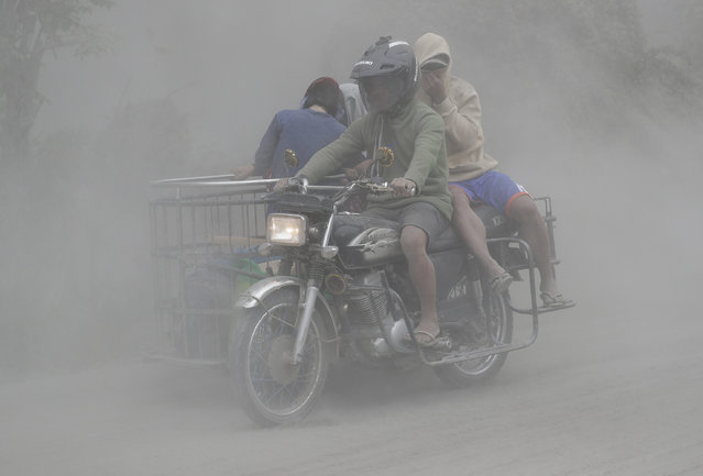 A family rides their motorcycle through clouds of ash as they evacuate to safer grounds as Taal volcano in Tagaytay, Cavite province, southern Philippines on Monday, January 13, 2020. Red-hot lava is gushing from the volcano after a sudden eruption of ash and steam that forced residents to flee and shut down Manila's airport, offices and schools. (Photo by Aaron Favila/AP Photo)
