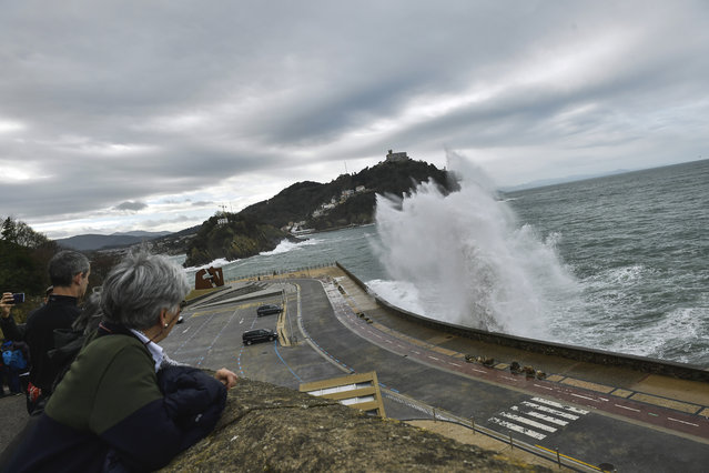 People look at a giant wave crashing against the sea defenses, during a high tide in San Sebastian, northern Spain, Sunday, December 22, 2019. Spain experienced high winds and heavy rain as a storm reached the northern Iberian Peninsula from the Atlantic. (Photo by Alvaro Barrientos/AP Photo)