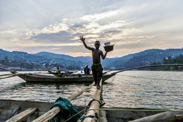 Izabayo, 13 years old, leaves the boat where he spent the night with 10 other fishermen after another fishing night at Lake Kivu, Rwanda on July 17, 2017. Izabayo has worked with the fishermen since he was 8 years old. (Photo by Natalia Jidovanu/AFP Photo)