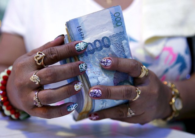 A casino financier wearing rings and with painted fingernails, counts money she collected from a gambler only moments before, in Angeles city, north of Manila, Philippines, in this May 25, 2015 file photo. (Photo by Erik De Castro/Reuters)