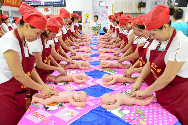 People participate in a free infant-care training course using model babies in Haikou, China on July 20, 2017. (Photo by Reuters/China Stringer Network)