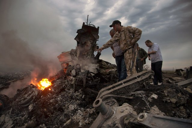 People inspect the crash site of a passenger plane near the village of Grabovo, Ukraine, Thursday, July 17, 2014. Ukraine said a passenger plane carrying 295 people was shot down Thursday as it flew over the country, and both the government and the pro-Russia separatists fighting in the region denied any responsibility for downing the plane. (Photo by Dmitry Lovetsky/AP Photo)