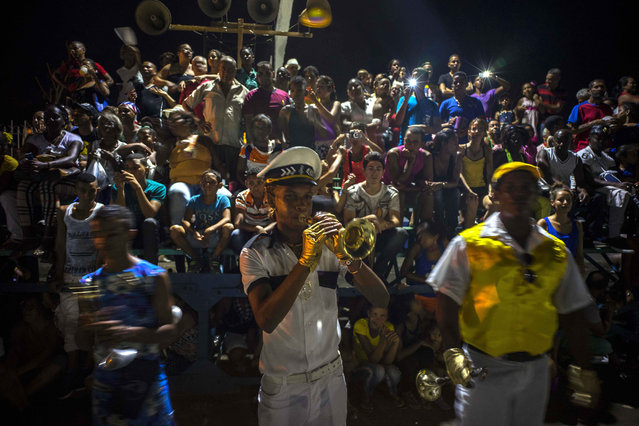 In this July 25, 2015 photo, a reveler plays the trumpet at the start of a carnival parade in Santiago, Cuba. Along with the new oceanfront Malecon and the restoration of homes in the city's historic center, the Cuban government has built a new theater and an artisanal brewpub as part of a broader reconstruction and improvement effort that began after Hurricane Sandy devastated the city in 2012. (Photo by Ramon Espinosa/AP Photo)