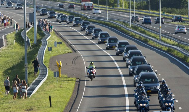 A row of hearses carrying victims of the Malaysia Airlines flight MH17 plane disaster are escorted on highway A27 near Nieuwegein by military police, on their way to be identified by forensic experts in Hilversum, July 23, 2014. The bodies of the first victims from the Malaysian airliner shot down over Ukraine last week arrived back in the Netherlands on Wednesday amid dignified grief tinged with anger. (Photo by Marco de Swart/Reuters)