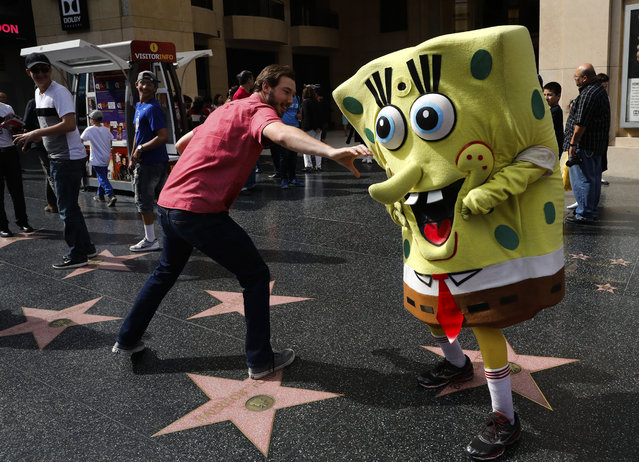 "In this Monday, April 17, 2017 photo, Belnarr Golden, wearing a SpongeBob SquarePants costume, dodges a tourist trying to pull the nose of his costume on Hollywood Boulevard, in Los Angeles. Longtime street performers say the business used to be more lucrative, until the boulevard became overpopulated with costumed characters. ""I crack jokes on them. That's my trick. I make them laugh"", said Golden. ""If I stand still, I'm not getting paid"". (Photo by Jae C. Hong/AP Photo)"