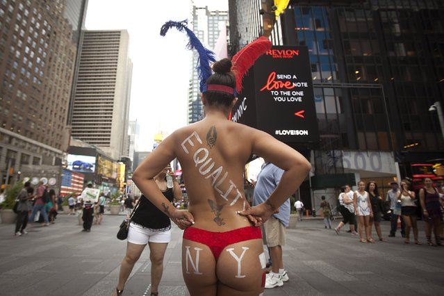 A woman who poses for tips wearing body paint and underwear poses for photos in Times Square in New York, August 19, 2015. (Photo by Carlo Allegri/Reuters)