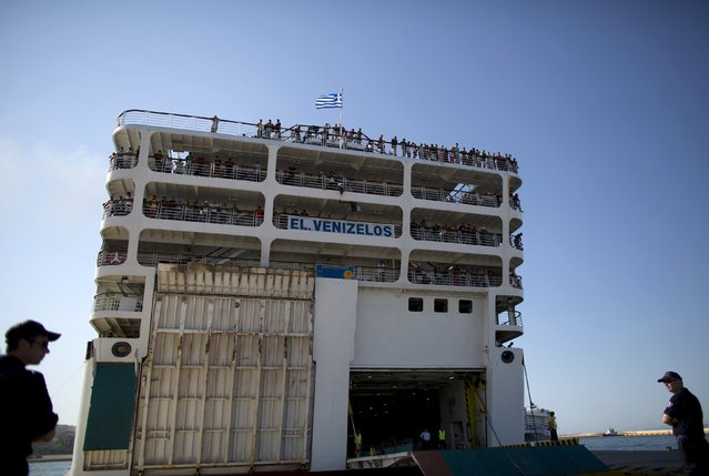 """Policemen stand guard as passenger ship """"Eleftherios Venizelos"""" carrying hundreds of Syrian refugees onboard arrives at the port of Piraeus near Athens, Greece, August 20, 2015. The ship was heading to the Greek mainland from islands in the Aegean Sea on Wednesday amid confusion over its final destination and the fate of passengers. (Photo by Stoyan Nenov/Reuters)"""