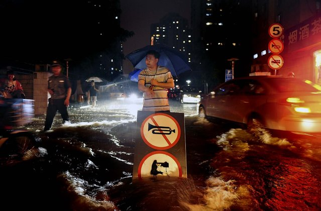 A man uses a signboard to signal motorists driving through flooded streets following the heaviest rains to hit Beijing in six decades on July 21, 2012. (Photo by Associated Press)