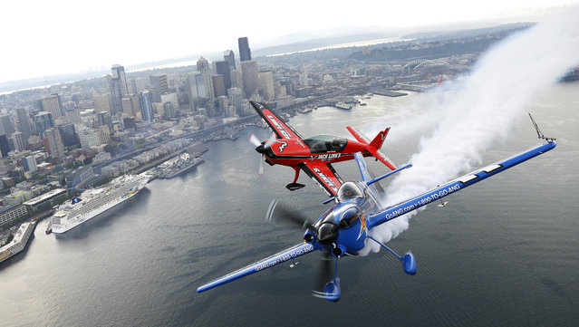 Pilots John Klatt, right, flying the blue Air National Guard MX-S airplane, and Jeff Boerboon, left, flying the red Jack's Links Extra 300L airplane, fly in formation Saturday, August 2, 2014, above Seattle. The two will perform Saturday and Sunday as part of the Boeing Seafair Air Show. (Photo by Ted S. Warren/AP Photo)