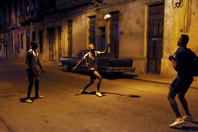 Street seller David Garcia (C), 20, plays with a soccer ball with his friends Luis Enrique (R), 20, who is attending military service, and Yaciel Concepcion, 21, who is a physics teacher, in downtown Havana, March 5, 2015. (Photo by Alexandre Meneghini/Reuters)