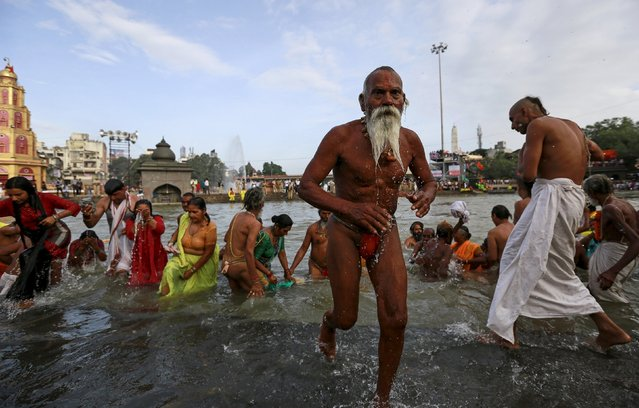 A Sadhu or a Hindu holy man leaves after taking a dip  in the Godavari river during the first Shahi Snan (grand bath) at Kumbh Mela, or Pitcher Festival in Nashik, India, August 29, 2015. Hundreds of thousands of Hindus took part in the religious gathering at the banks of the Godavari river in Nashik city at the festival, which is held every 12 years in different Indian cities. (Photo by Danish Siddiqui/Reuters)