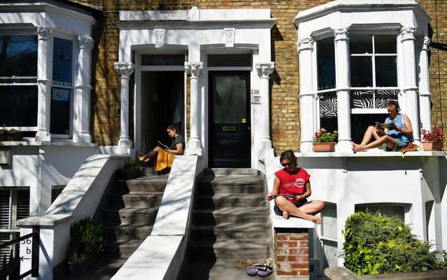 People sit on their doorsteps in Islington, as the spread of the coronavirus disease (COVID-19) continues, London, Britain, April 5, 2020. (Photo by Dylan Martinez/Reuters)