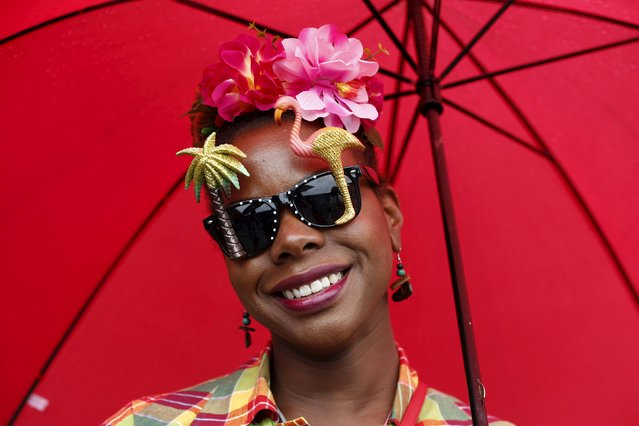 A performer poses for a photograph under her umbrella at the Notting Hill Carnival in west London, August 31, 2015. (Photo by Eddie Keogh/Reuters)