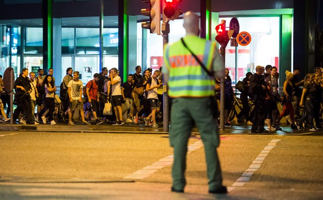 People are evacuated from the area around the shopping mall Olympia Einkaufzentrum OEZ in Munich on July 22, 2016 after gunmen  went on a shooting rampage in the busy shopping centre, killing eight people in a suspected terror attack. The southern city was in lockdown after the shootings, which saw panicked shoppers fleeing the Olympia mall as armed anti-terror police roamed the streets in search of the assailants. (Photo by AFP Photo/Stringer)