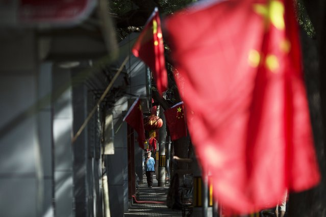 A woman walks under Chinese flags decorating a hutong in central Beijing September 2, 2015 as people in the capital prepares to mark the end of World War Two. (Photo by Damir Sagolj/Reuters)