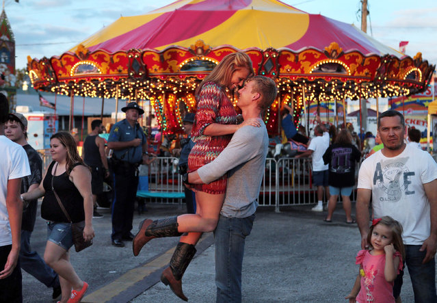 In this Thursday, August 7, 2014 photo, A.J. Pfeifer, 24, lifts his girlfriend Beth Crow, 20, so their friend can make a photo of them in front of the carousel on the opening day of the Missouri State Fair on Thursday, August 7, 2014, in Sedalia, Mo. The couple came to the fair to listen to the Nace Brothers concert. (Photo by Laurie Skrivan/AP Photo/St. Louis Post-Dispatch)