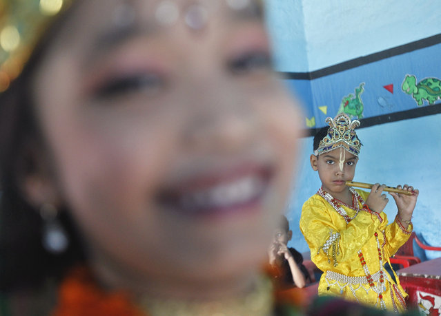 A schoolboy dressed as Lord Krishna rehearses for his performance inside a classroom during the celebrations to mark Janmashtami festival in New Delhi August 27, 2013. (Photo by Anindito Mukherjee/Reuters)