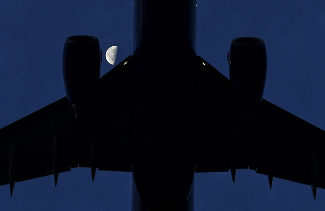 A half moon is seen from Gravelly Point as a jet takes off from Ronald Reagan National Airport on August 14, 2017 in Arlington, Va. (Photo by Ricky Carioti/The Washington Post)