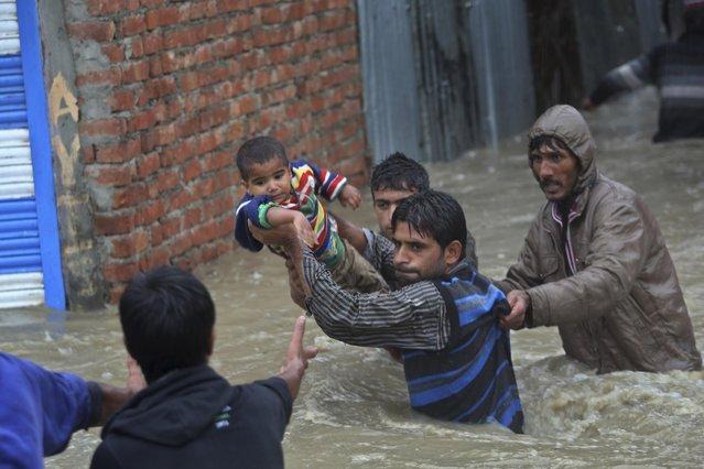 Kashmiri men carry a boy to safety after their neighborhood was flooded in Srinagar, India, Thursday, September 4, 2014. (Photo by Dar Yasin/AP Photo)
