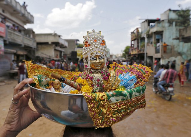 A devotee carries an idol of Hindu god Krishna in a container on her head during celebrations to mark the Hindu festival of Janmashtami in Ahmedabad, India, September 6, 2015. (Photo by Amit Dave/Reuters)