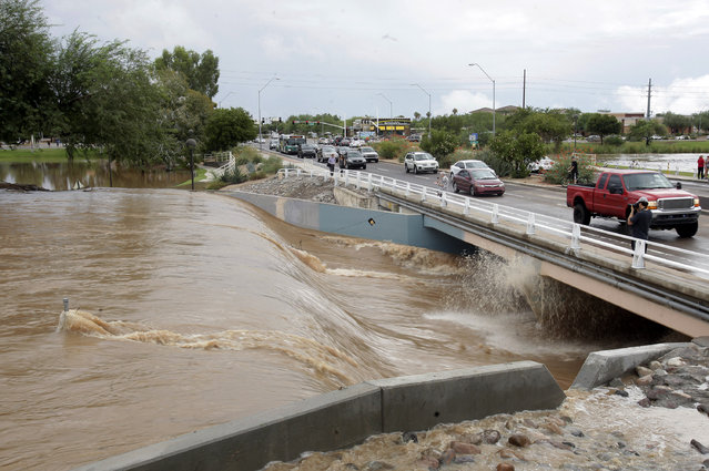 Cars drive by flooding Monday, September 8, 2014, in Scottsdale, Ariz. (Photo by Rick Scuteri/AP Photo)