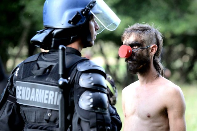 An environmental activist confronts a riot policeman securing a construction site in the Sivens forest, as clearing has started in preparation of the Sivens dam construction, on September 9, 2014 near Gaillac, in the Tarn region. Although the construction of the dam would help supply water to nearby farms, it would remove a 13 hectares long reservoir of biodiversity. Proponents of the dam – including the FDSEA (Departemental Federation of syndicated farmers) – deemed necessary to secure water supplies for farmers. (Photo by Remy Gabalda/AFP Photo)