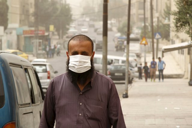 A man wearing a face mask walks on a street during a sandstorm in downtown Amman, Jordan, September 8, 2015. (Photo by Majed Jaber/Reuters)