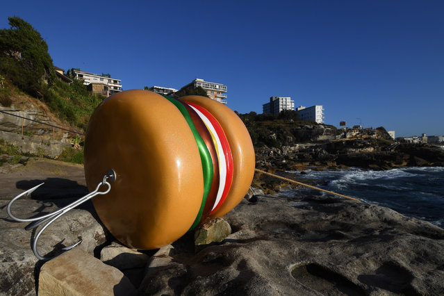"""""""What a Tasty Looking Burger"""" by James Dive at Sculpture By The Sea on October 18, 2017 in Sydney, Australia. """"Beware, the fish are now fishing"""". The annual art event draws tens of thousands of visitors from Sydney and across Australia and the world to the famous Bondi Beach. This year the outdoor exhibition celebrates its 21st birthday with 104 exhibiting artists from Australia and around the world and runs from the 19th October-5th November 2017. (Photo by Dean Lewins/AAP)"""