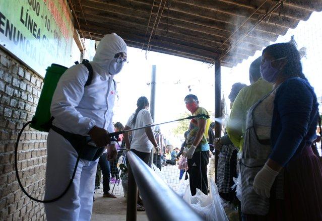 A health worker sprays disinfectant on a woman outside the Palmasola prison amid the coronavirus disease (COVID-19) outbreak in Santa Cruz, Bolivia on May 18, 2020. (Photo by Rodrigo Urzagasti/Reuters)