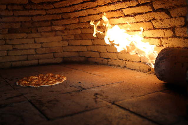 """Iraqi traditional dish """"Lahm Bajin"""" is baked inside a traditional oven in central Erbil city, northern Iraq, September 13, 2014. (Photo by Mohamed Messara/EPA)"""