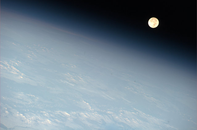 The moon appears near the earth's horizon in a photo of an orbital moonset taken from aboard the International Space Station on May 17, 2011. (Photo by Ron Garan/Reuters/NASA)