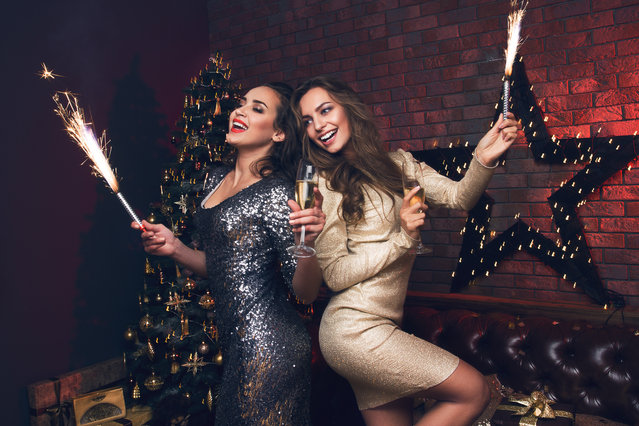 Two young women dancing in dress with a champagne at club on New Year. Christmas party. Christmas day 2017. (Photo by Stacestock/Getty Images)