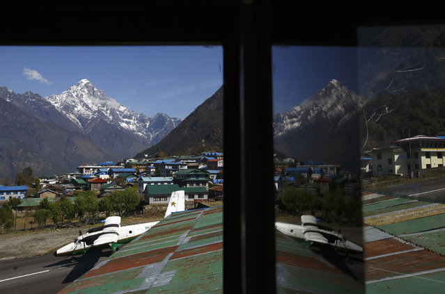 An aircraft is reflected in a mirror at a hotel as it takes off from Tenzing Hillary Airport, which has a reputation as the world's most dangerous airport in Lukla, approximately 9186 feet above sea level in Solukhumbu district April 25, 2014. (Photo by Navesh Chitrakar/Reuters)
