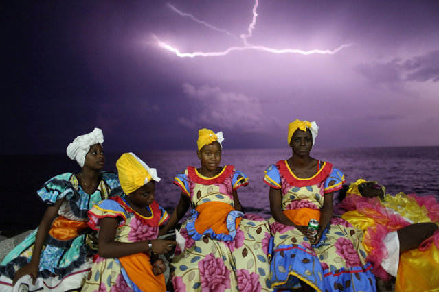 Revellers chat on Havana's Malecon seafront before performing at a carnival parade, Cuba, August 12, 2016. (Photo by Alexandre Meneghini/Reuters)